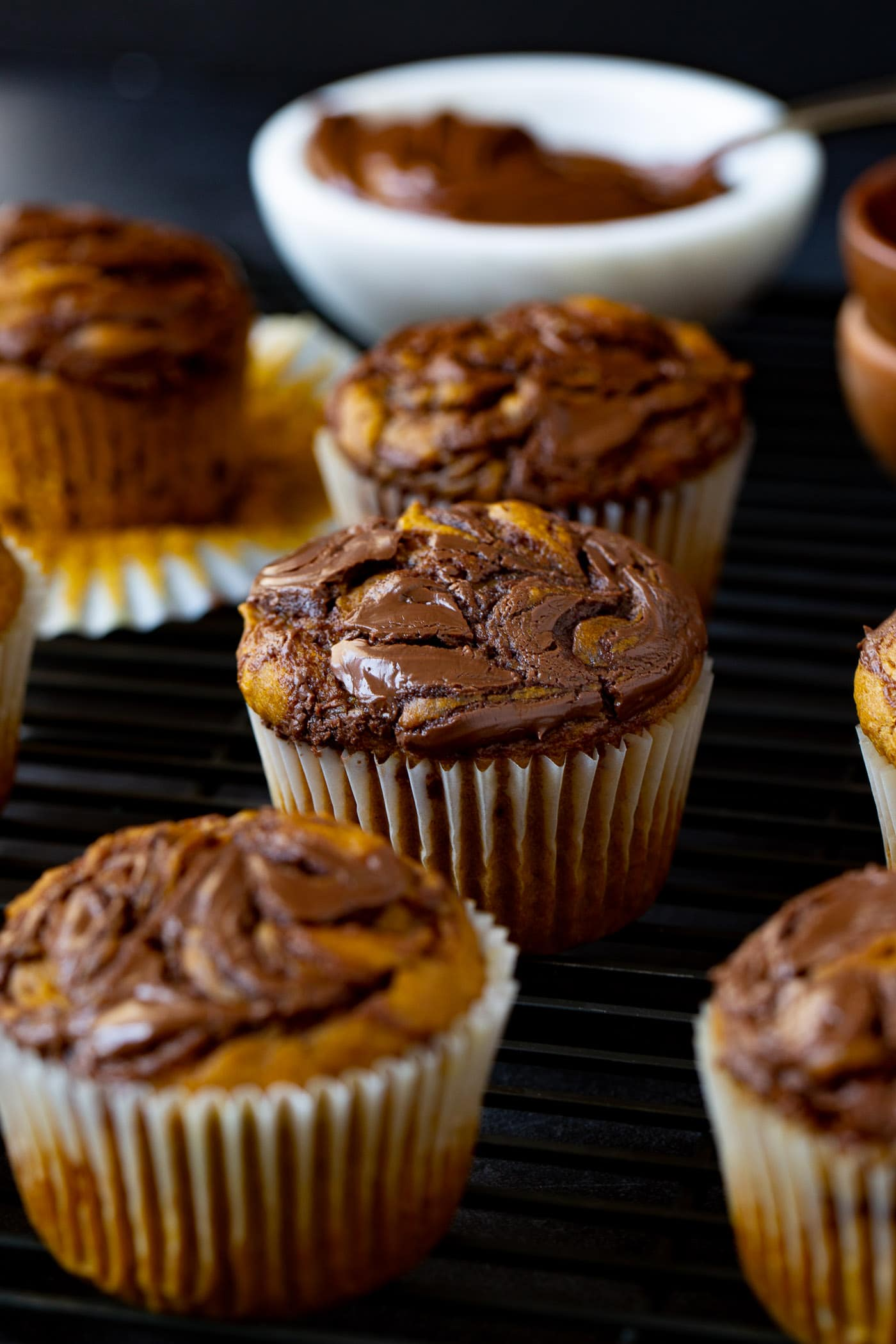 Nutella swirled pumpkin muffins. The paper liner has been peeled back on one muffin so you can see the pumpkin with the nutella swirled in it.