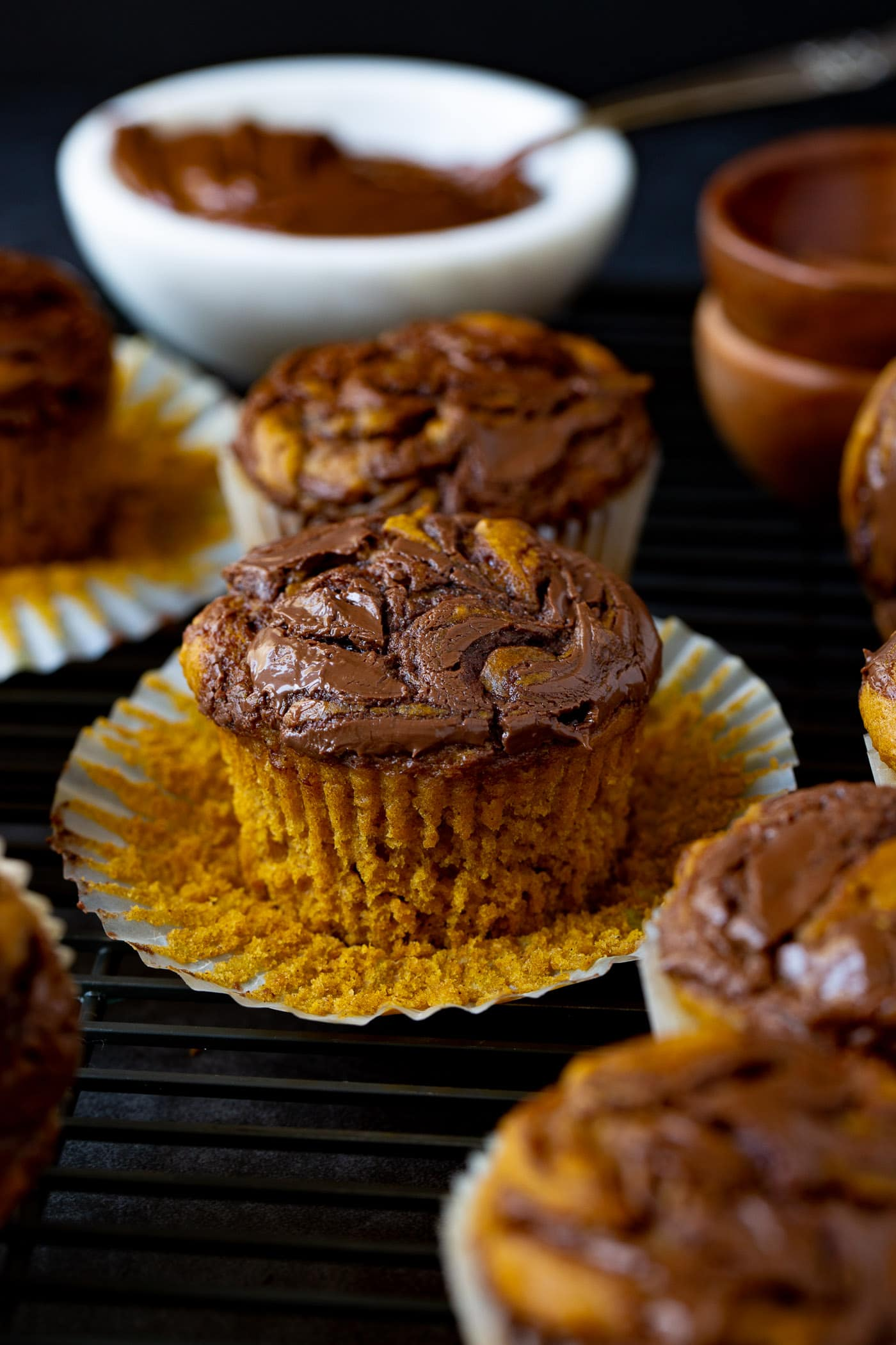 Nutella swirled pumpkin muffins. The paper muffin liners are peeled back so you can see the soft pumpkin muffin with the nutella swirled through it.