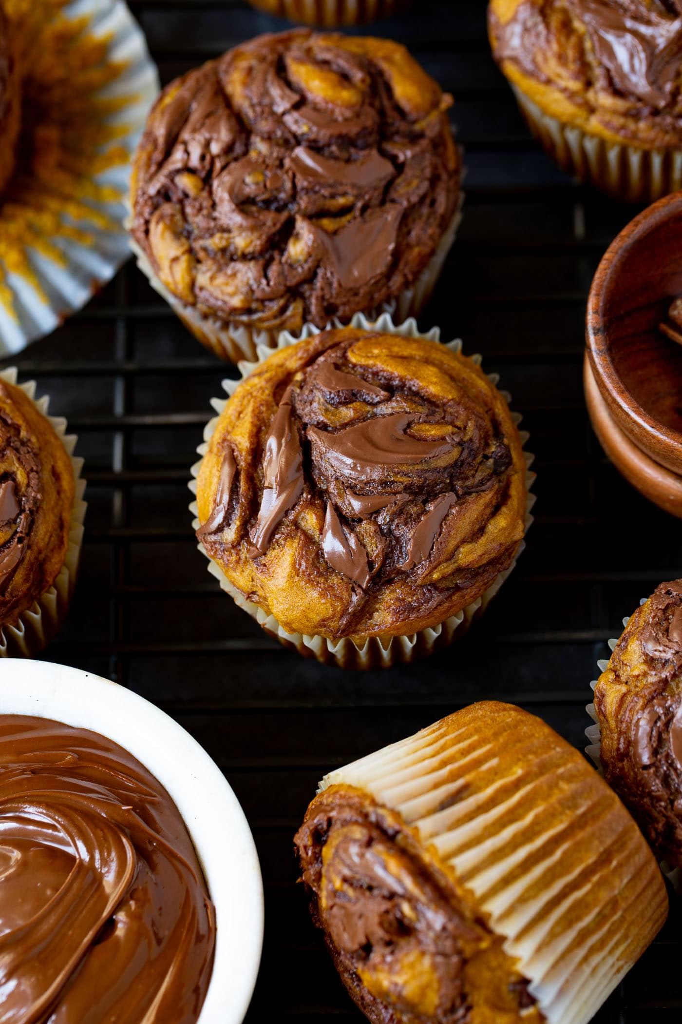 Nutella swirled pumpkin muffins. Nutella has been swirled through the muffin before being baked. A small bowl of Nutella sits next to the muffins.