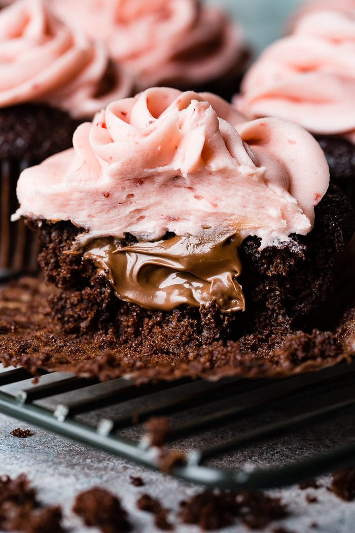 a close up of a nutella stuffed chocolate cupcake with strawberry buttercream frosting