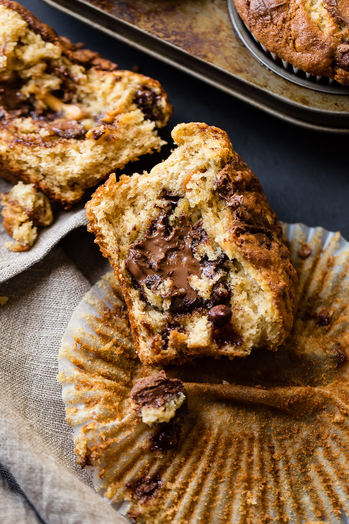 a sliced open peanut butter nutella stuffed banana muffin sitting on an open muffin liner