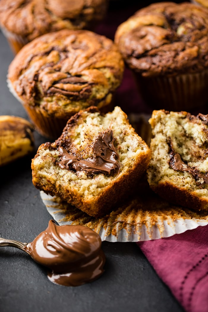 Nutella swirled banana muffins surrounding a cut open muffin with nutella coming out the center with a spoonful of nutella in the front