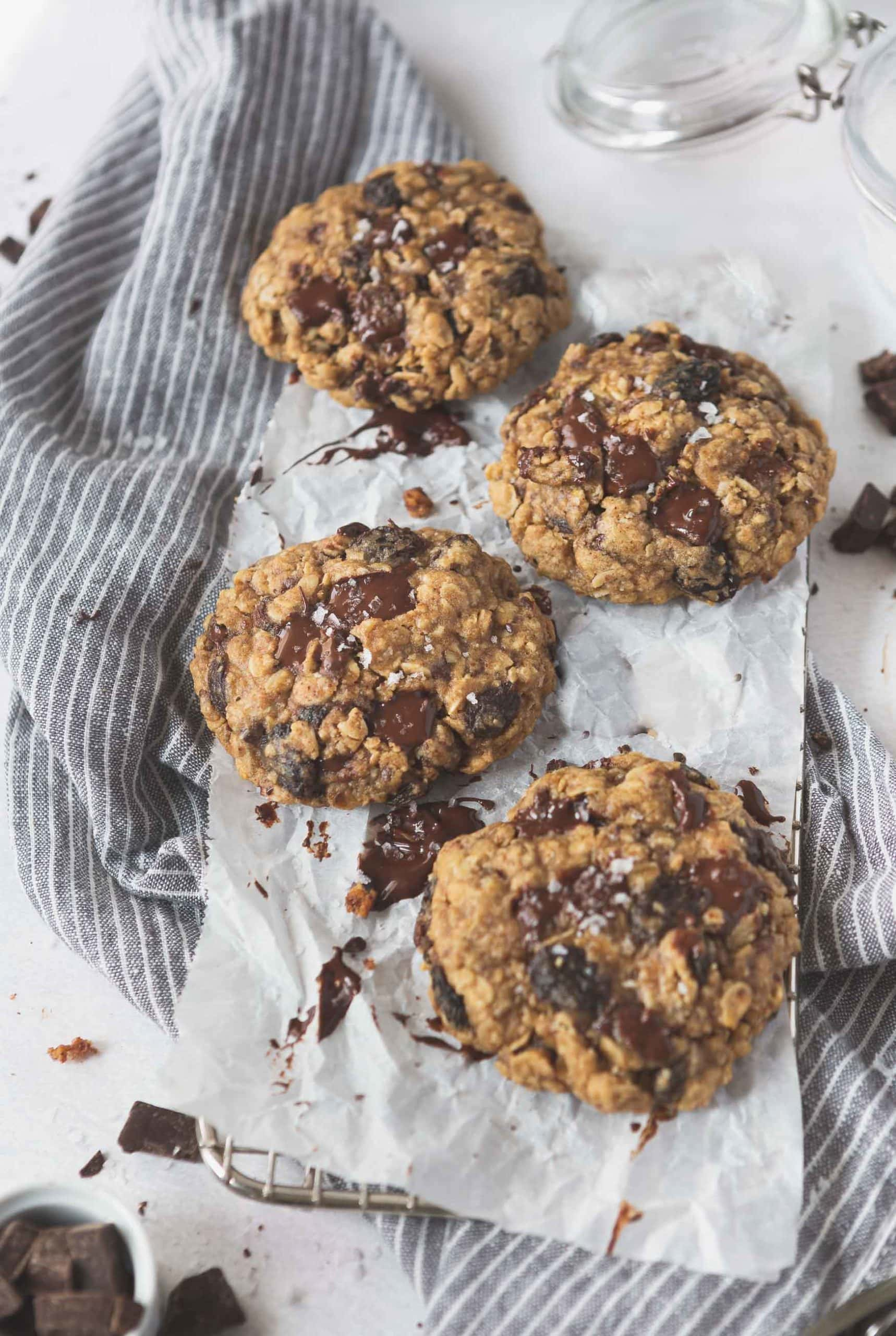 Four oatmeal raisin chocolate chip cookies. There are raisins and chocolate chunks in the cookies, and they are on parchment paper with chunks of melted chocolate around the cookies.