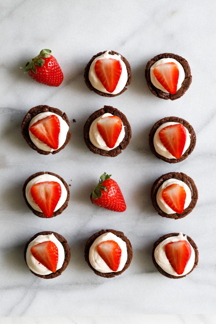 A marble background with a white plate filled with tiny brownie cups filled with a white chocolate cream cheese filling and a sliced strawberry on top making these the cutest tuxedo brownie cups