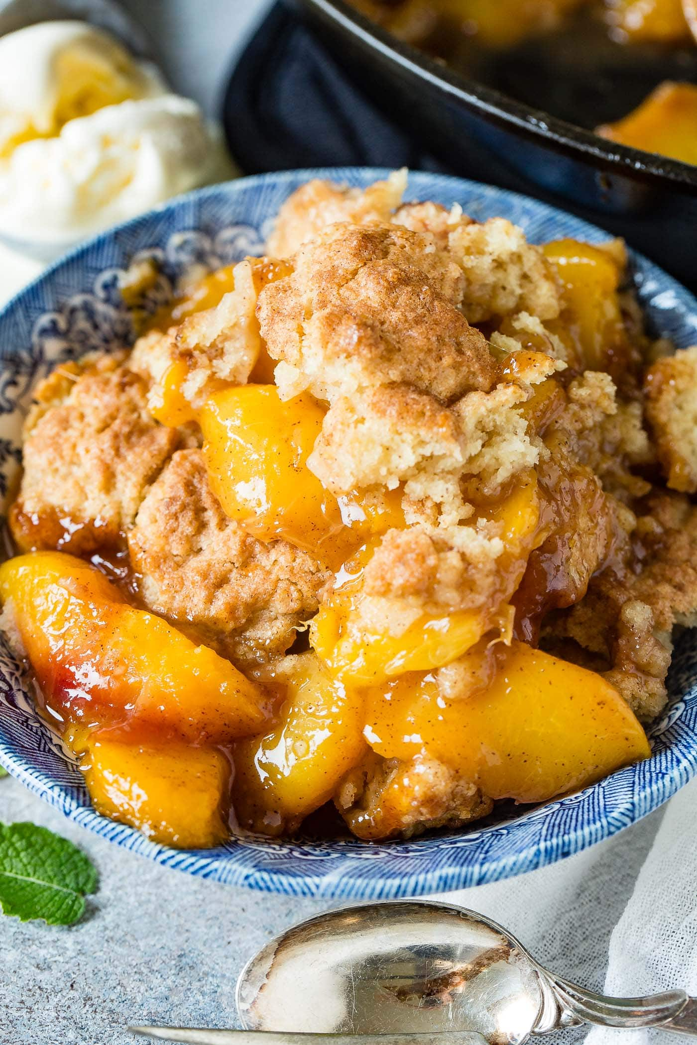 Picture of a bowl of peach cobbler with a layer of biscuits.
