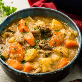 A photo of a bowl of beef stew with chunks of beef, potatoes, and carrots, and garnished with fresh parsley.