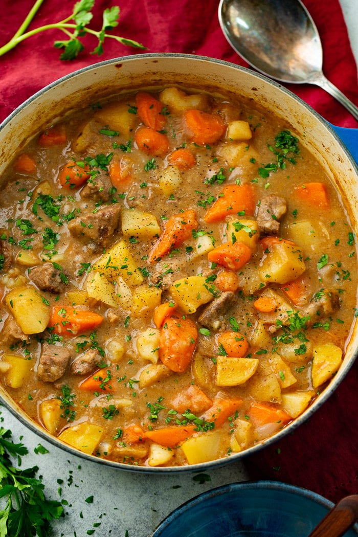 A photo of a dutch oven full of cooked beef stew containing beef chunks, potatoes, and carrots and garnished with chopped fresh parsley.