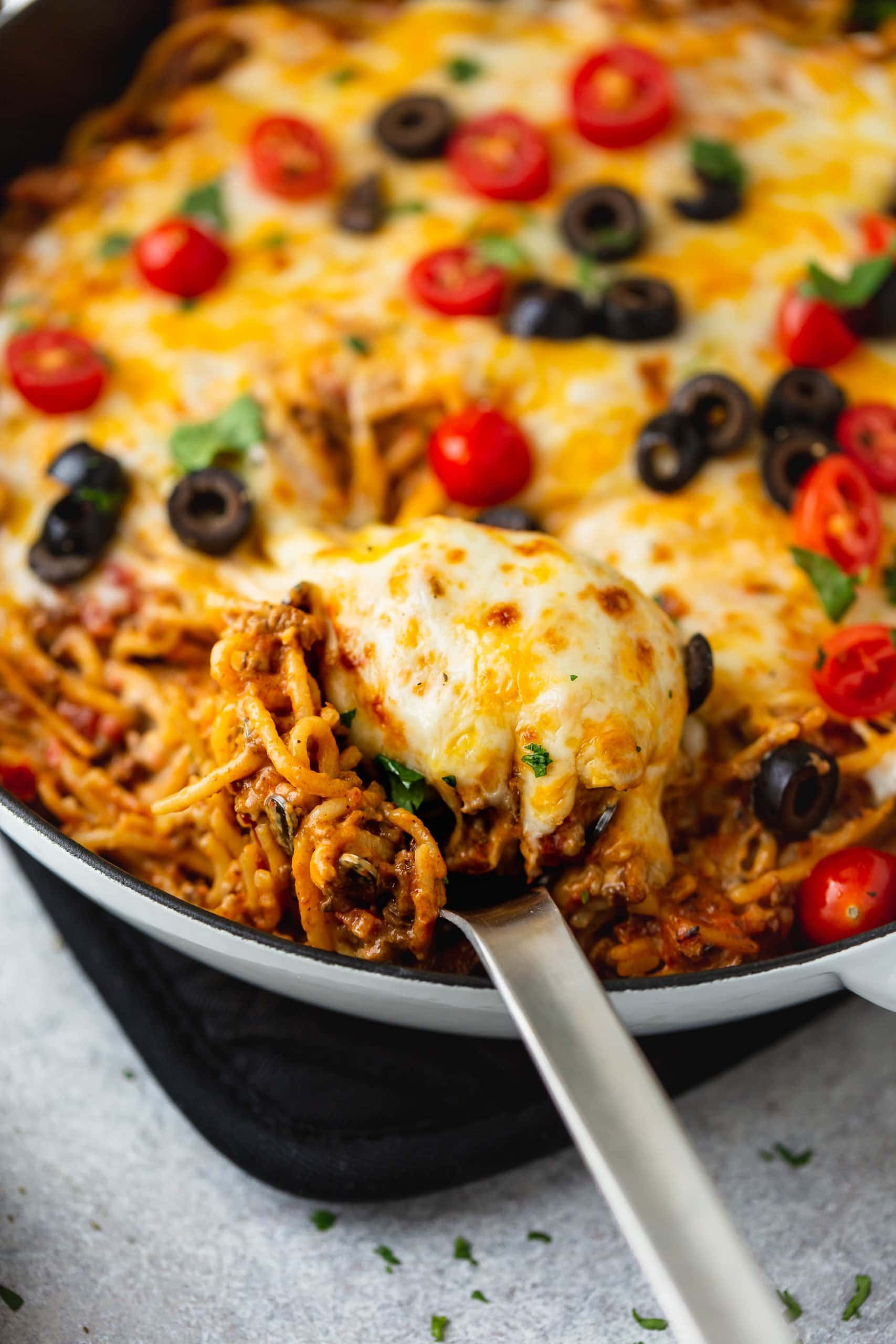A skillet full of cheesy ground beef taco spaghetti. A serving spoon is in the pot and the spaghetti is topped with melted cheese, tomatoes, olives, green onions and cilantro.