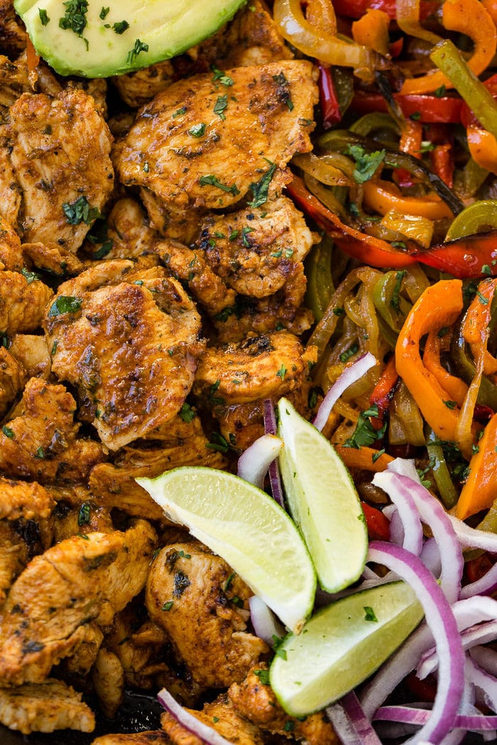 A closeup photo ofchicken fajita filling - cooked chicken, sauteed peppers and onions, lime wedges, sliced purple onion, and sliced avocados.