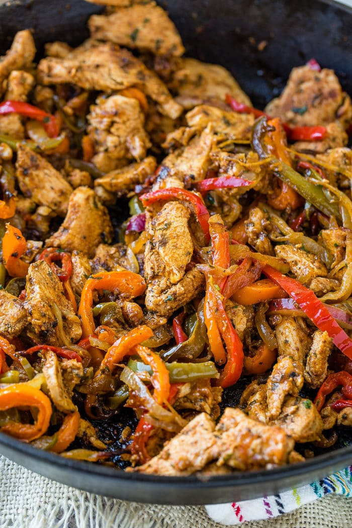 A photo of a cast iron skillet full of chicken fajita filling - cooked chicken and sauteed peppers and onions