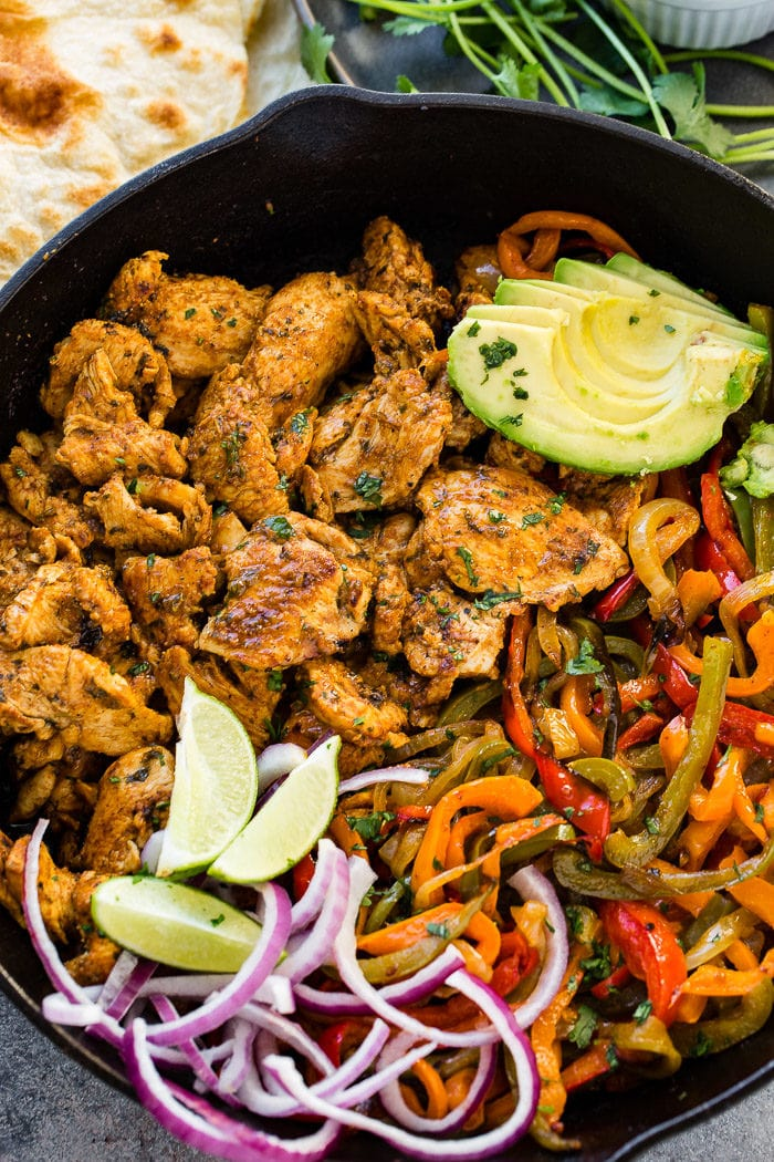 A photo of a cast iron skillet full of chicken fajita filling - cooked chicken, sauteed peppers and onions, lime wedges, sliced purple onion, and sliced avocados.