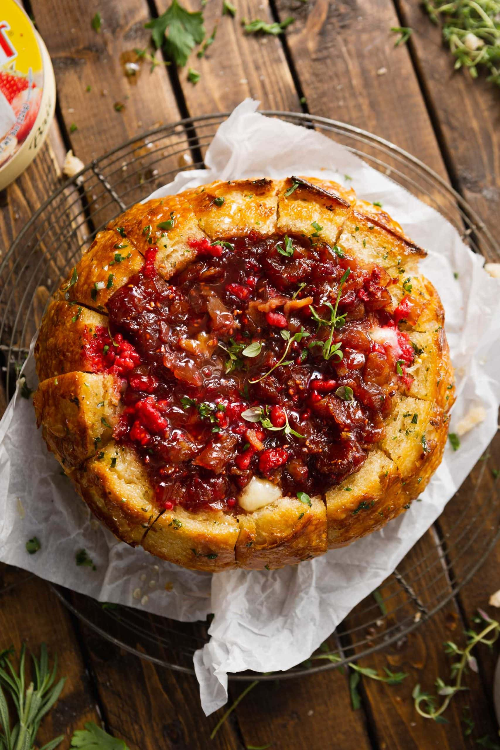 A bread bowl that has the center scooped out and it is filled with brie and topped with a raspberry and onion jam. The bread is resting on a piece of parchment paper.