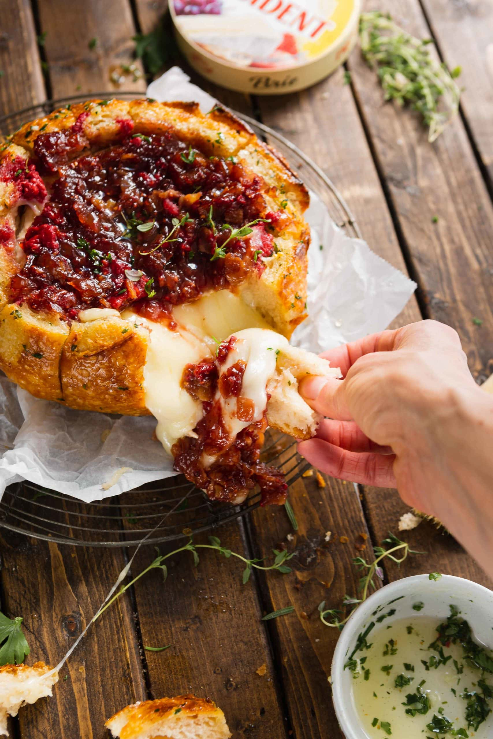 A piece of bread is being pulled apart from a bread bowl filled with baked brie and topped with onion jam and raspberries. The bread bowl is sitting on a piece of parchment paper.