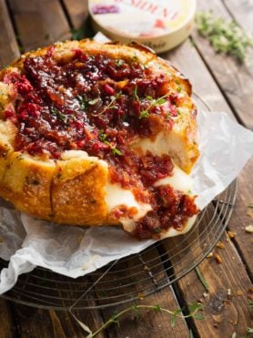 A bread bowl filled with brie and topped with onion jam and raspberries. It has been baked until it is golden brown and the cheese is melted.