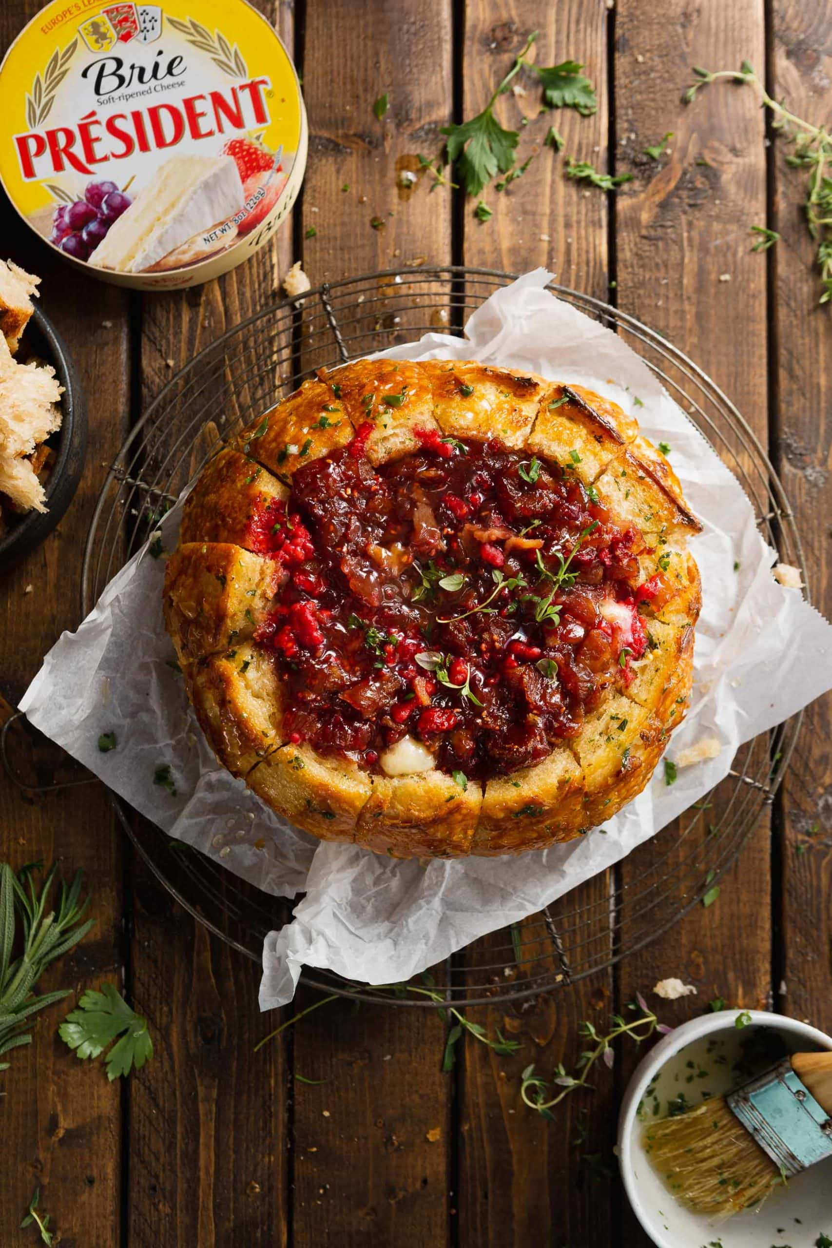 A bread bowl filled with brie and topped with a raspberry onion jam.