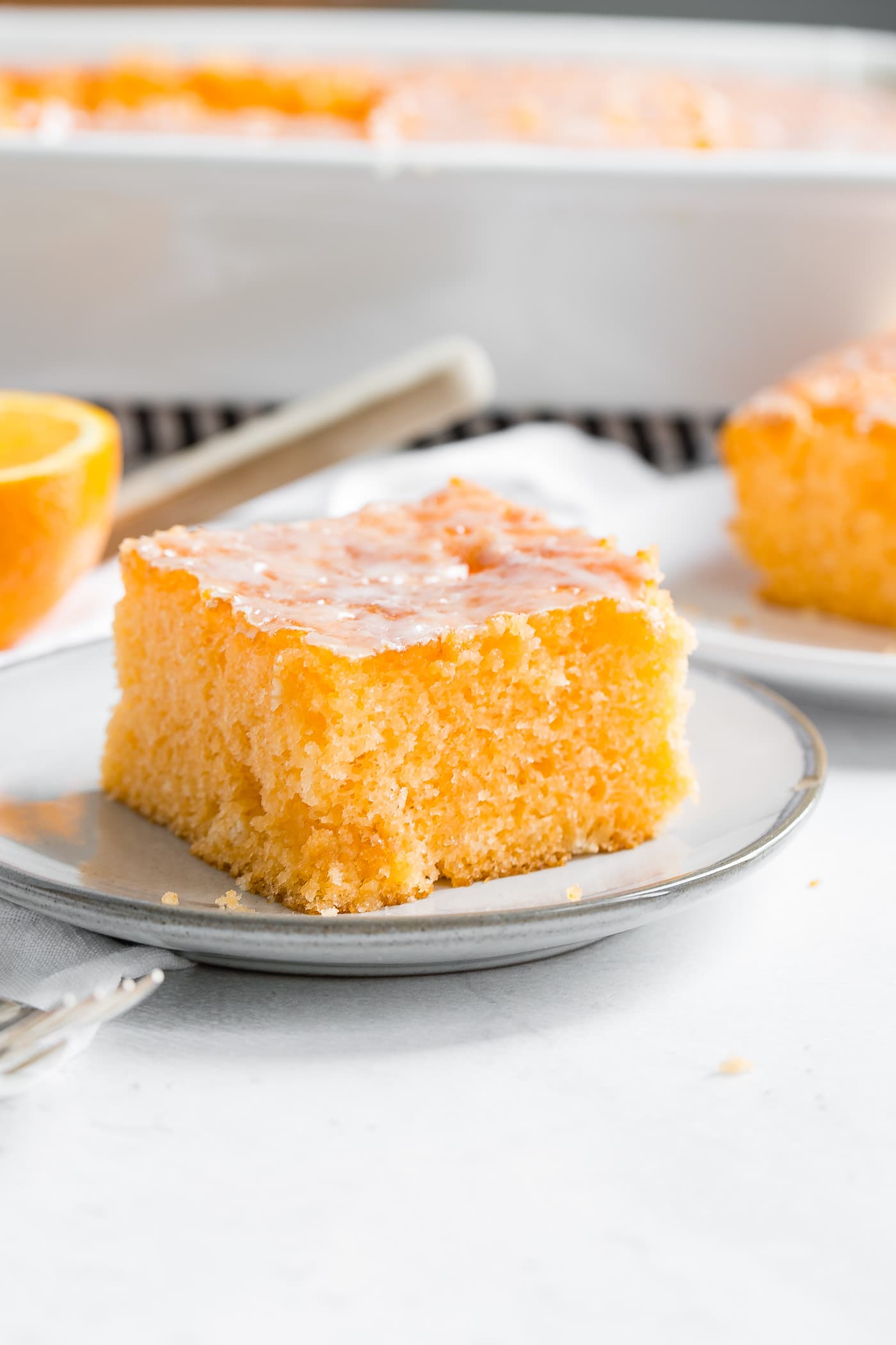 A photo of a piece of orange jello cake on a small white plate.