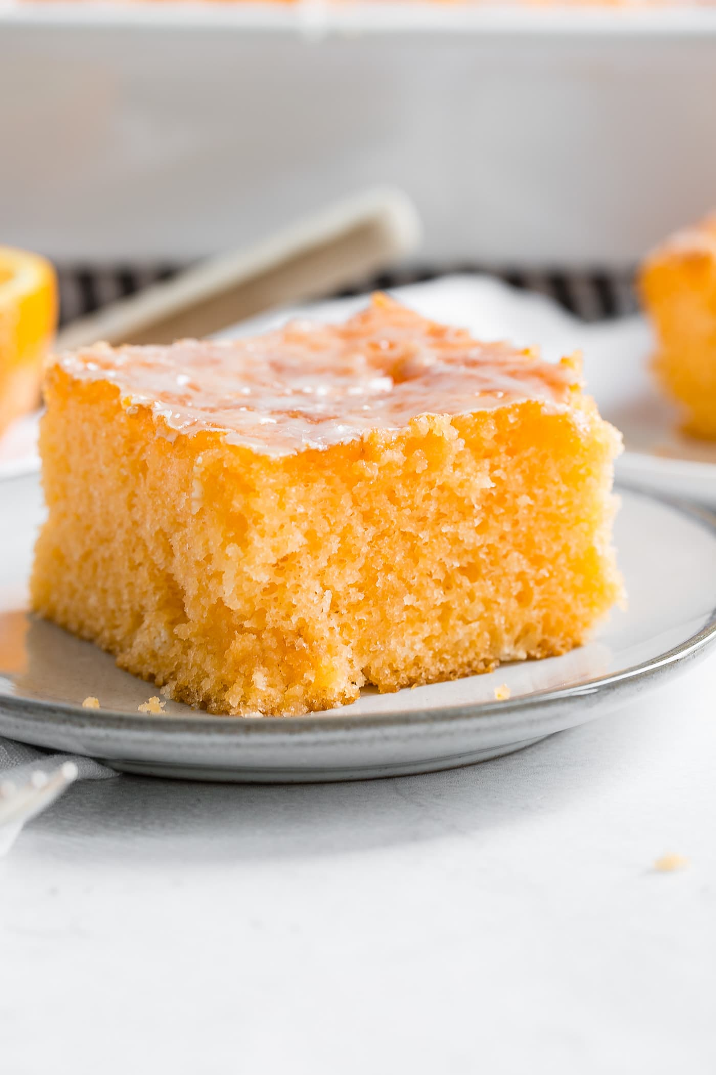 A photo of a piece of orange jello cake on a small white plate with orange glaze on the top.