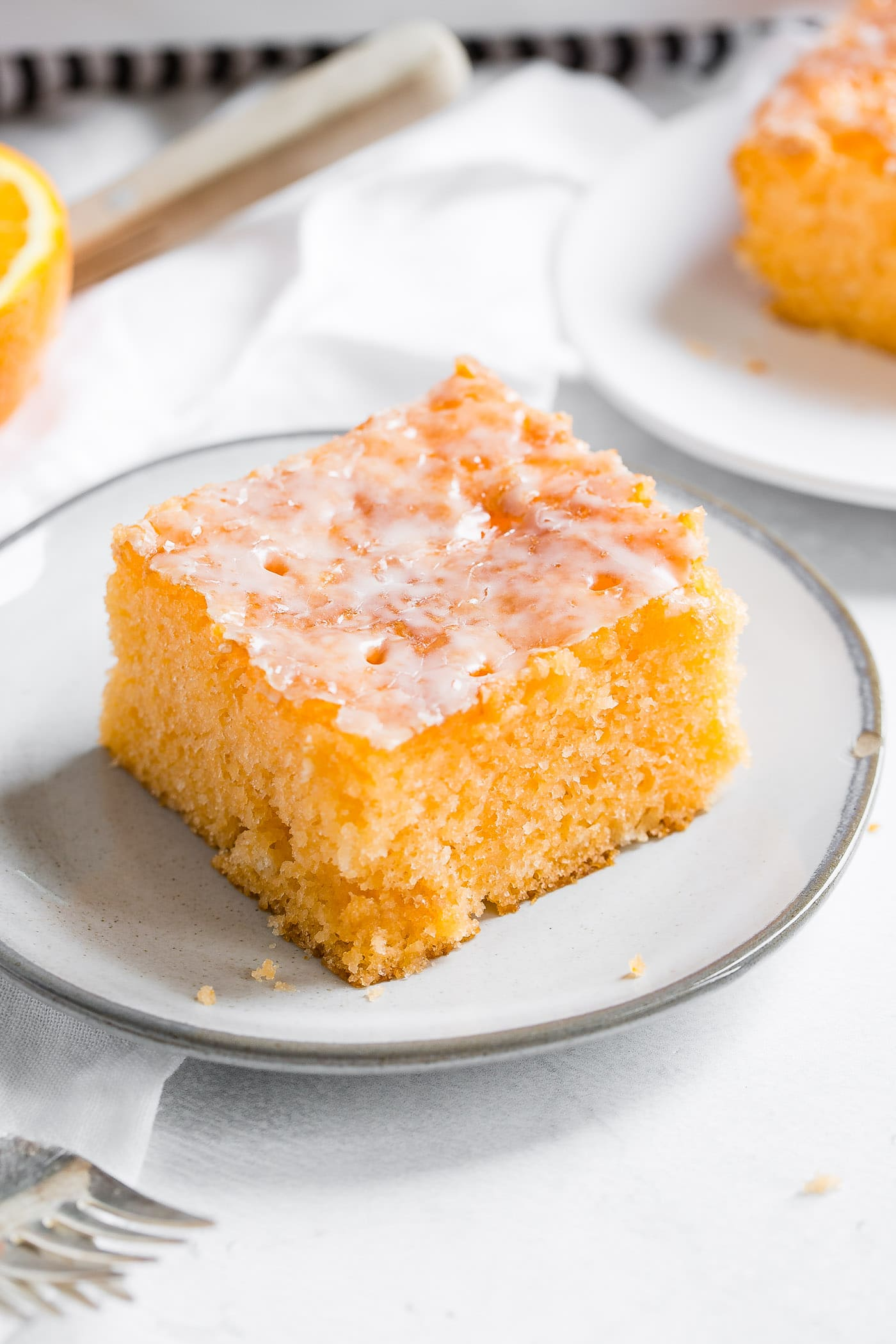 A photo of a piece of orange jello cake on a small white plate with another serving in the background and a fork in the foreground.