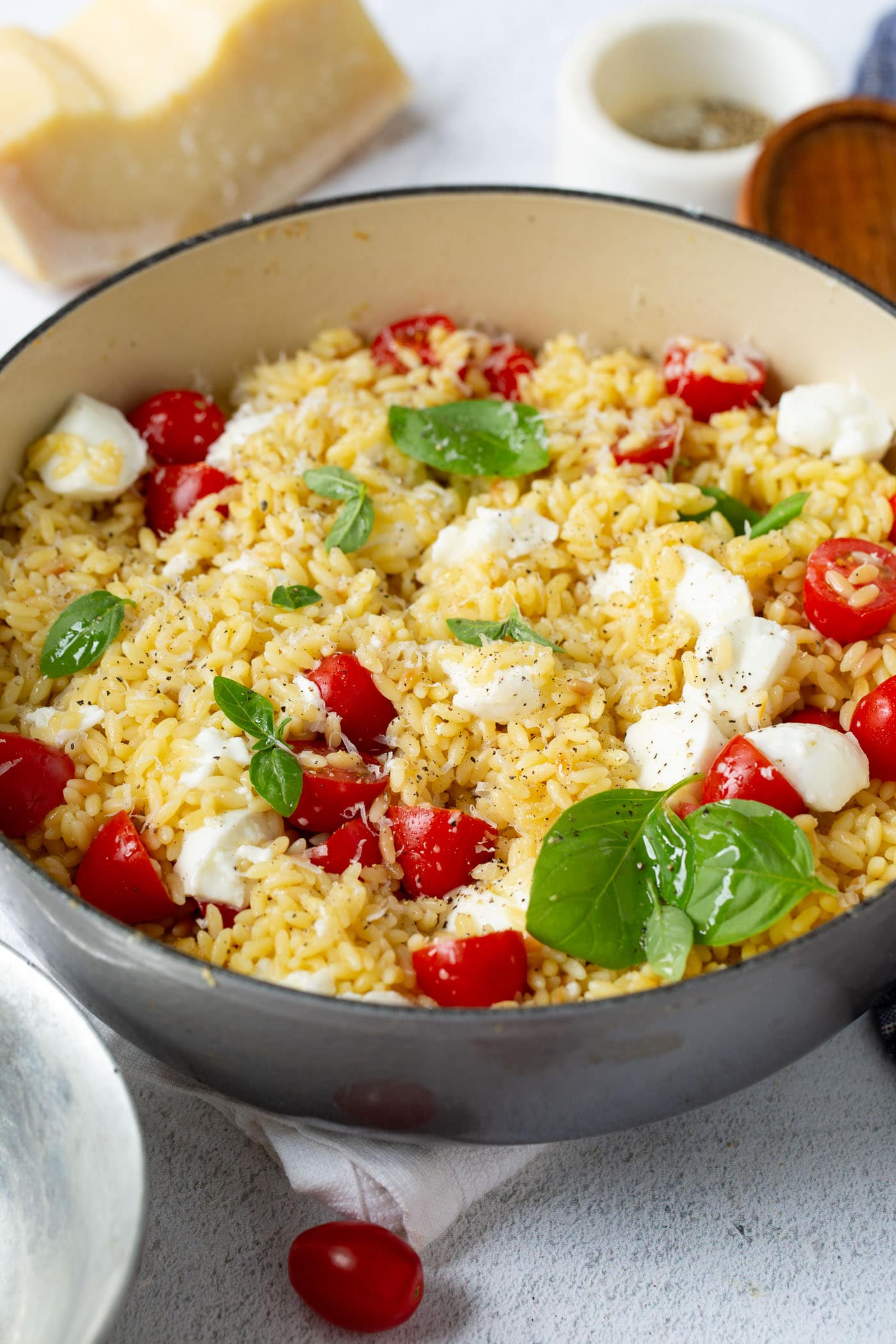 Caprese orzo salad in a larch serving bowl. There are bright red tomatoes, fresh green basil and chunks of mozzarella cheese. A few tomatoes, a brick of parmesan cheese, and a container of salt are on the table by the salad.