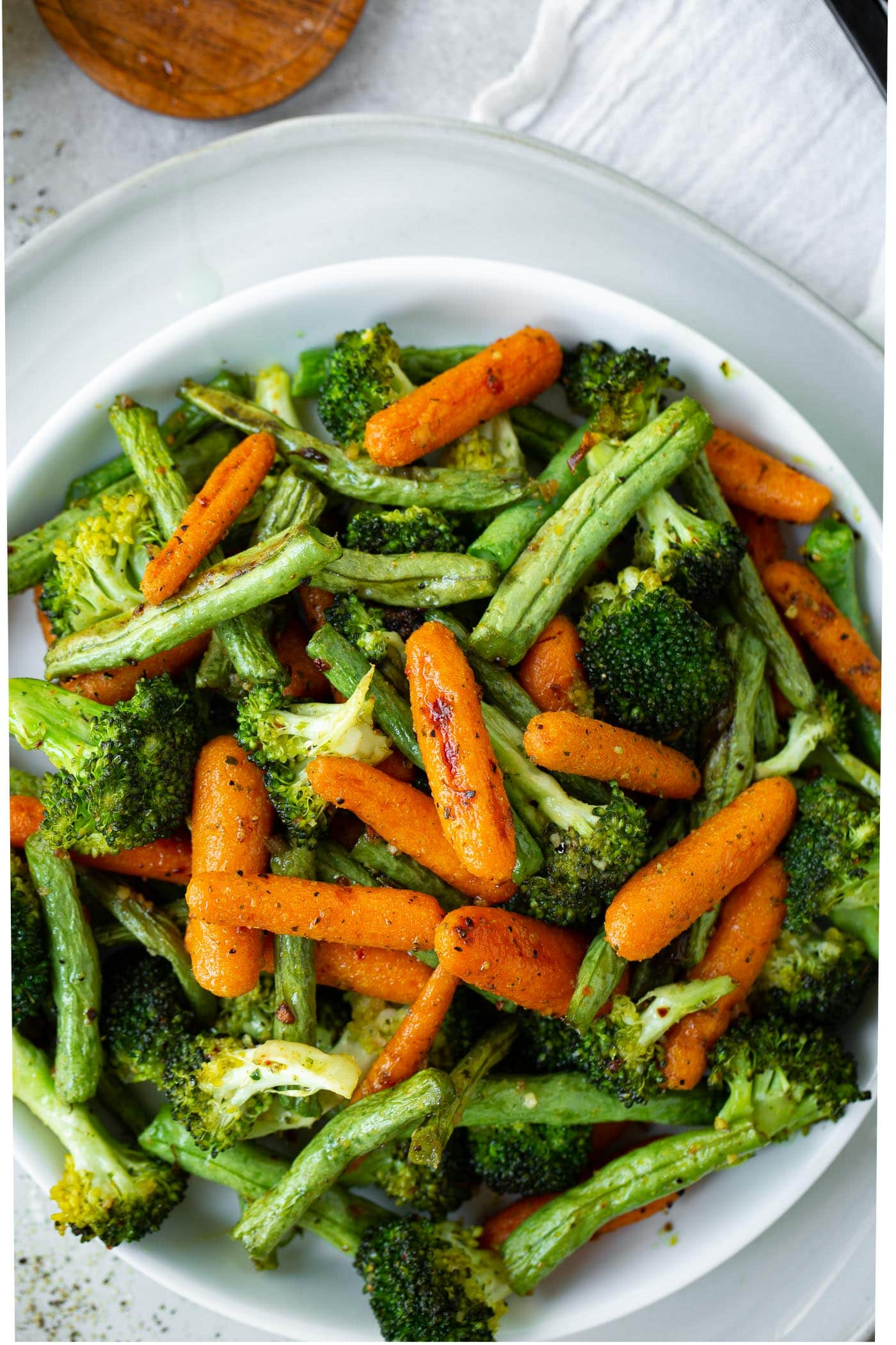 a photo of a roasted vegetable medley in a white serving bowl.