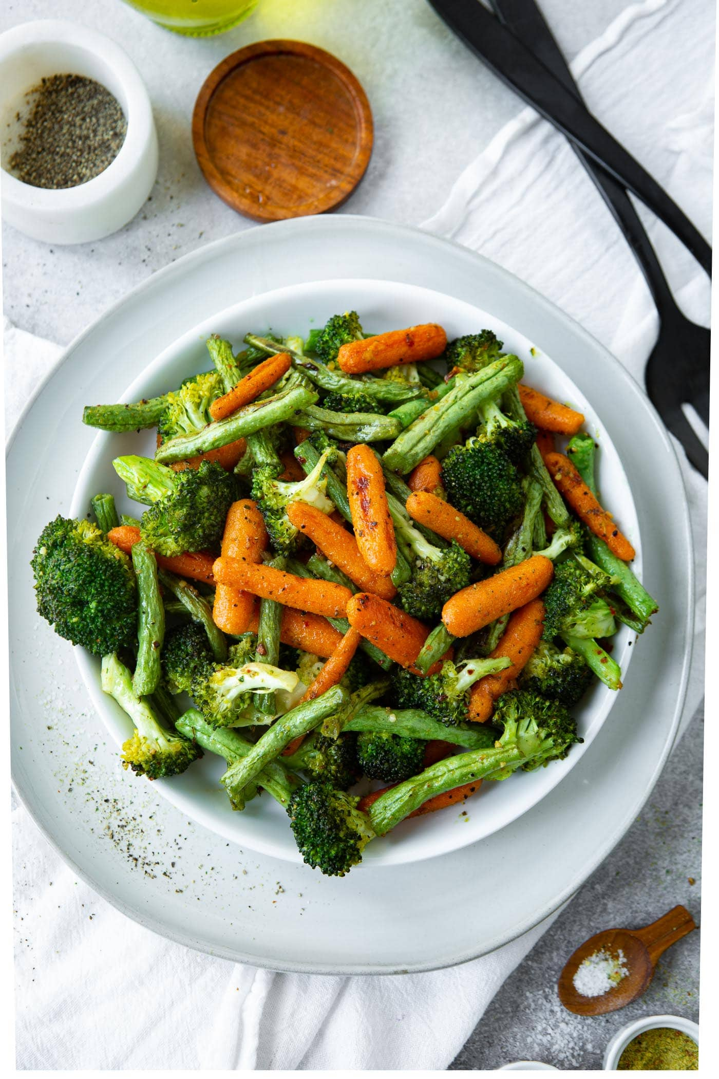 a photo of roasted baby carrots, green beans and broccoli in a white serving bowl on a white table cloth.