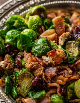 A vintage, silver bowl with flower full of bright green brussels sprouts that have been halved and pan roasted until golden brown on one side, olive oil and seasoning covering all of them and tossed with red craisins, crisp bacon and crunchy candied pecans ohsweetbasil.com