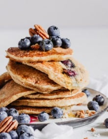 a stack of blueberry pecan pancakes with a drizzle of maple syrup