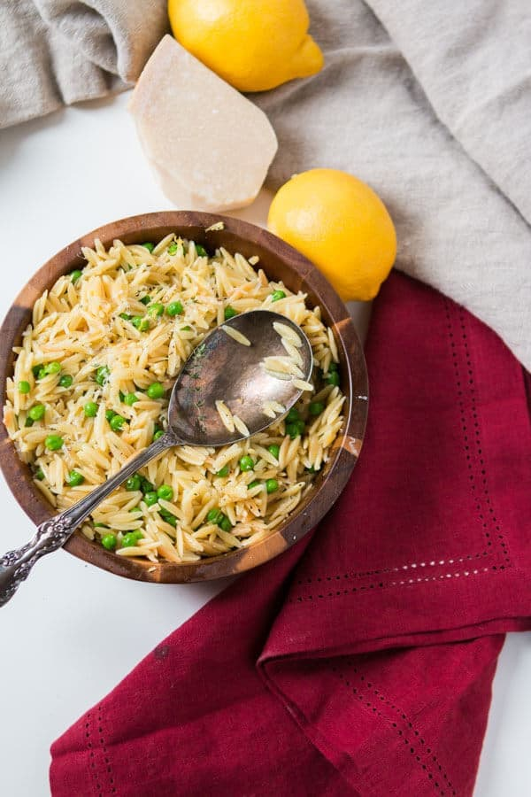 Simple lemon orzo with parmesan and peas with a silver spoon next to lemons, parmesan cheese and a red cloth.