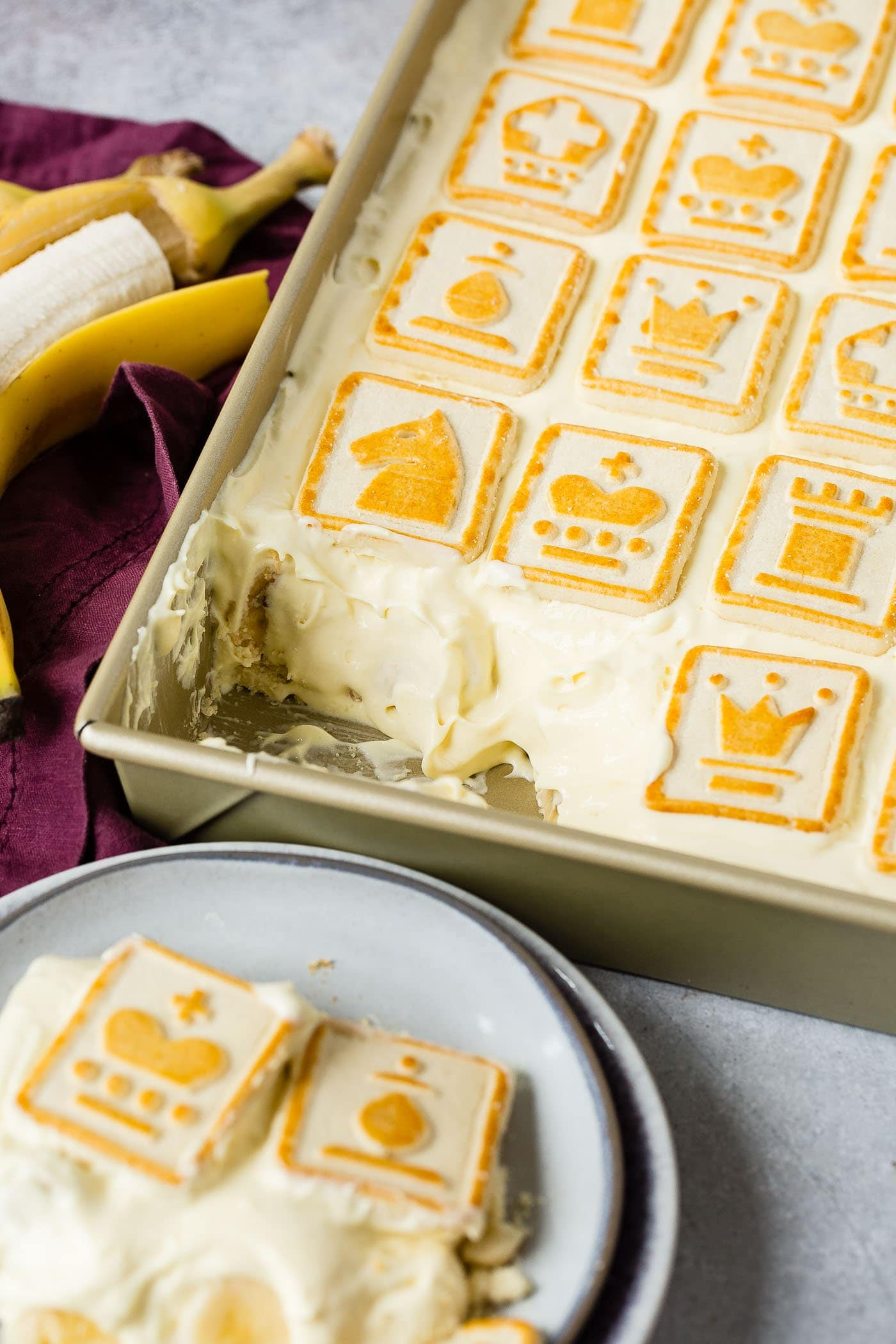A cake pan filled with Paula Deen's Not Yo Momma's Banana Pudding. A serving has been removed and put on a dessert plate. There are buttery chessman cookies covering the top. A peeled banana is next to the pan of pudding.