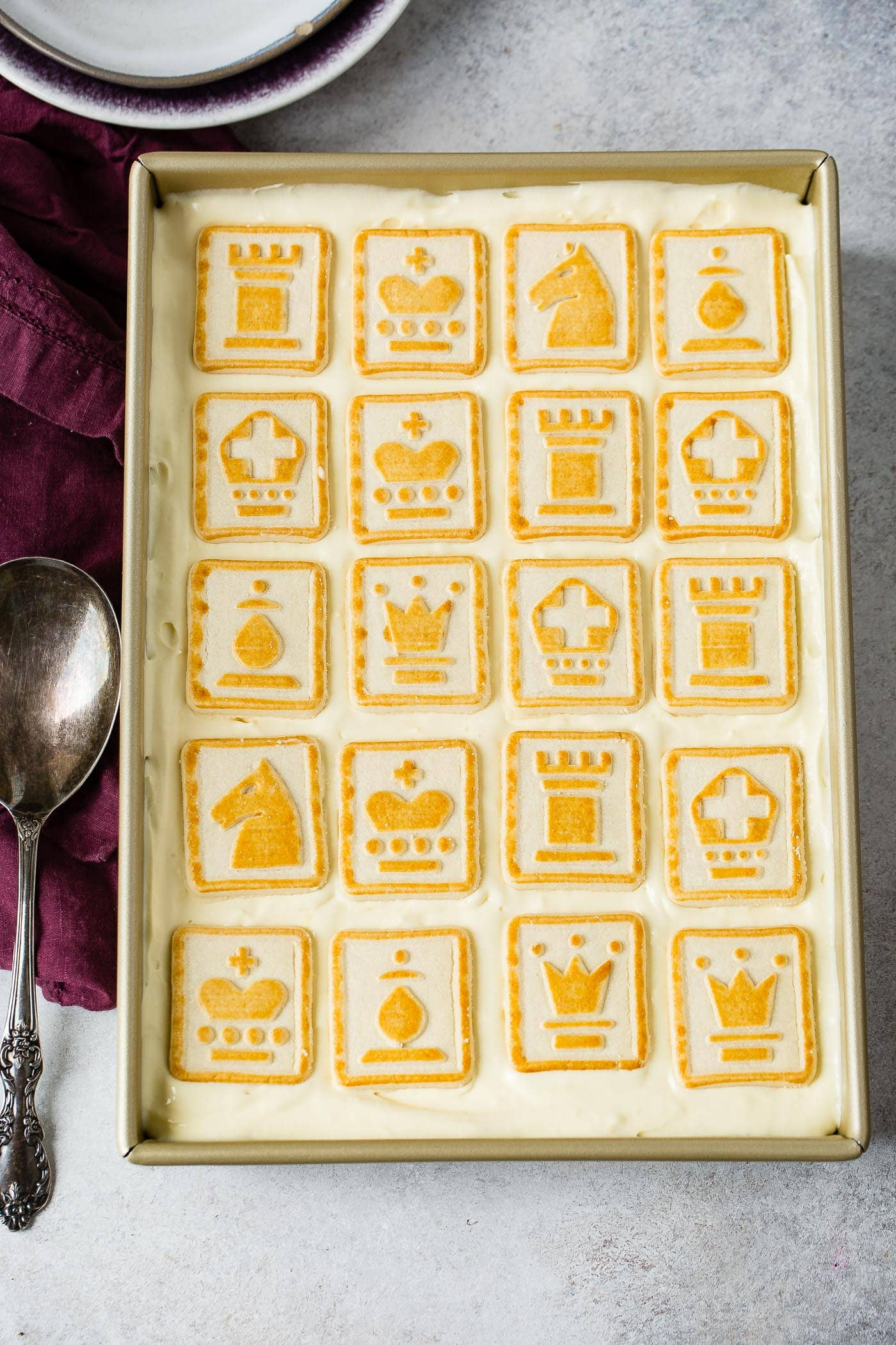 A pan of banana pudding covered with chessman cookies. The cookies are light in color and trimmed with yellow.