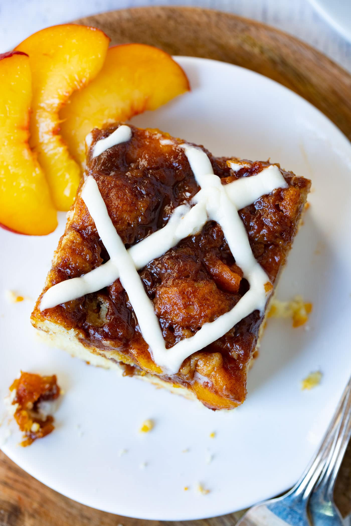 Picture of a peacock one-piece coffee cake covered in sweet glaze sitting on a white plate with three peach slices sitting next to it.