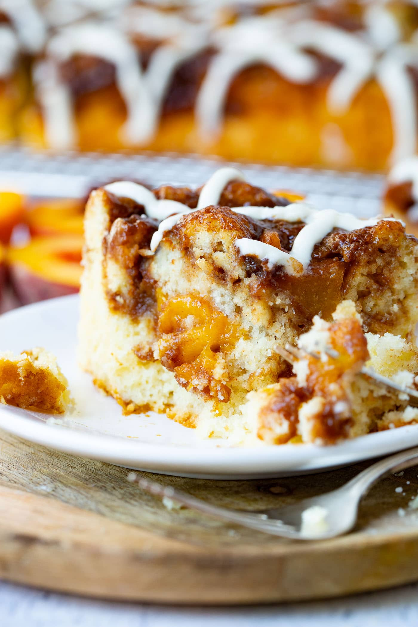 Photo of one piece of peach coffee cake that was cut with a fork