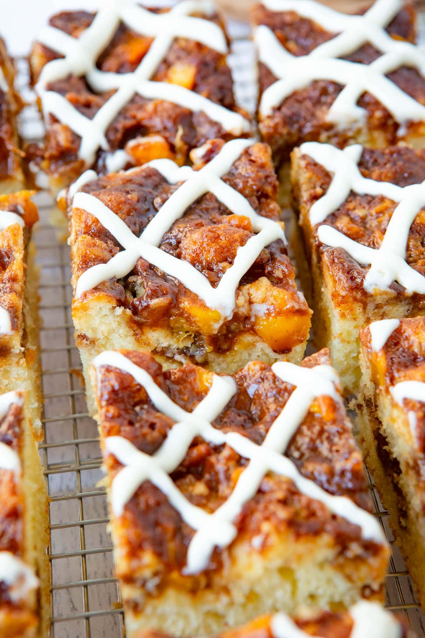 Several pieces of peach coffee cake with sweet glaze on top