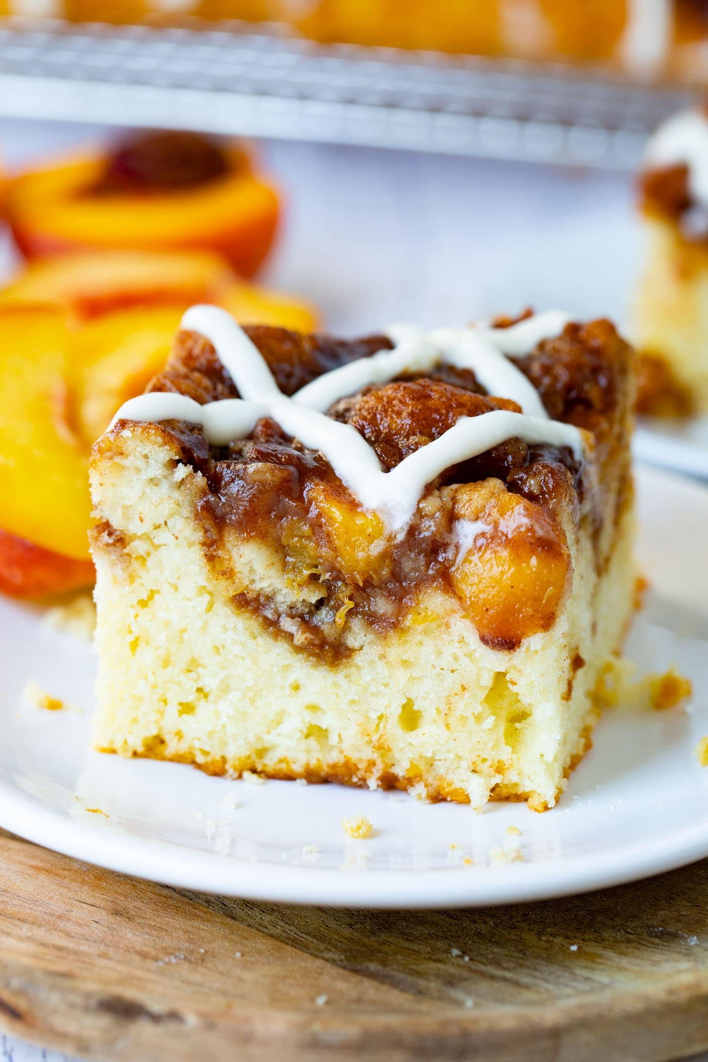 Picture of a single piece of peach coffee cake on a white plate with a sweet glaze on top of the cake