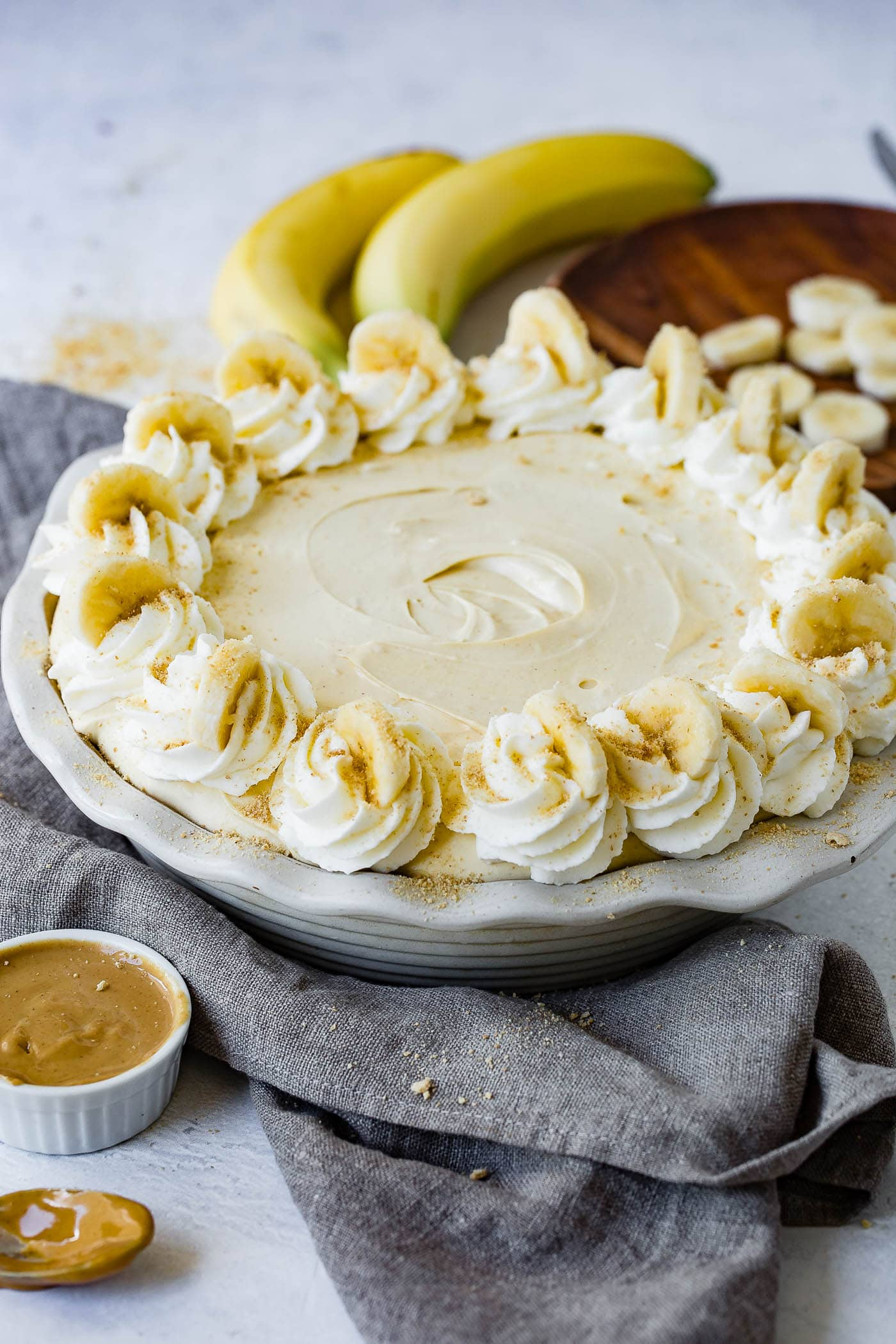 A peanut butter banana cream pie with whipped cream and bananas around the edge. There are bananas and peanut butter in the background.