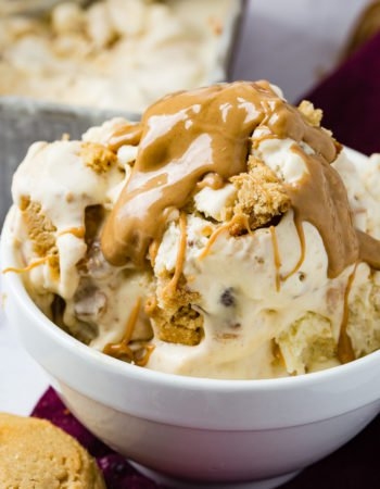 A photo of a bowl of homemade peanut butter cookie ice cream drizzled with creamy peanut butter one top and full of cookie chunks.