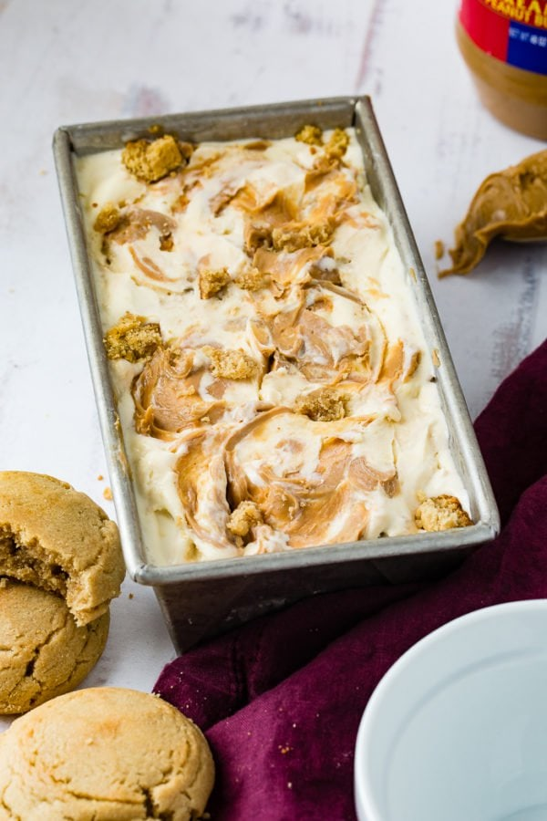 A phone of a pan of homemade peanut butter cookie ice cream drizzled with creamy peanut butter one top and full of cookie chunks.