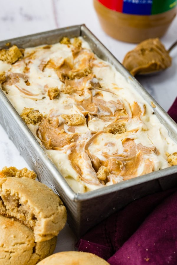 A photo of a pan of homemade peanut butter cookie ice cream drizzled with creamy peanut butter one top and full of cookie chunks.