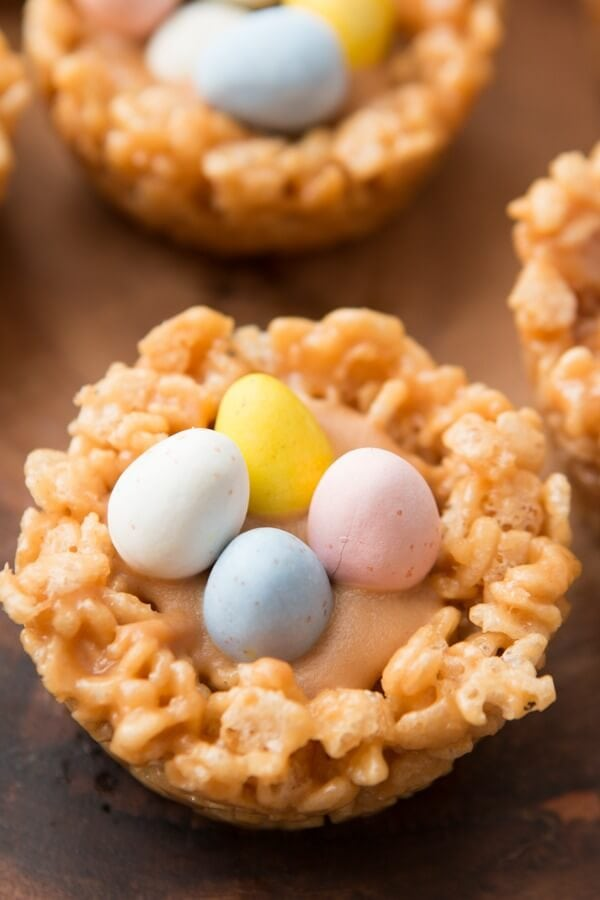 Spring is here! These beautiful Peanut Butter Rice Krispy Nests with Chocolate Eggs are as delicious as they are cute. Peanut butter chips, Rice Krispies, and Cadbury Eggs... what's not to love?! Peanut Butter Cream Filled Rice Krispy Nests with mini Cadbury Eggs ohsweetbasil.com Easter dessert, spring, no-bake