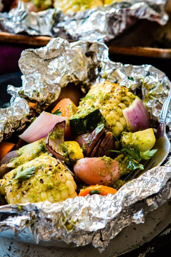 Want to know how to make foil packets for the grill? We love these pesto butter veggie foil packets for the grill as it can be hard to find good sides for bbqs and grilling. A few fresh ingredients to make a pesto butter, lots of veggies and a couple pieces of foil is all you need for a yummy side dish on the grill! ohsweetbasil.com corn, potatoes, onions, carrots, squash