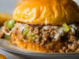 A photo of a philly cheesesteak sloppy joe on a toasted brioche bun on a white plate.