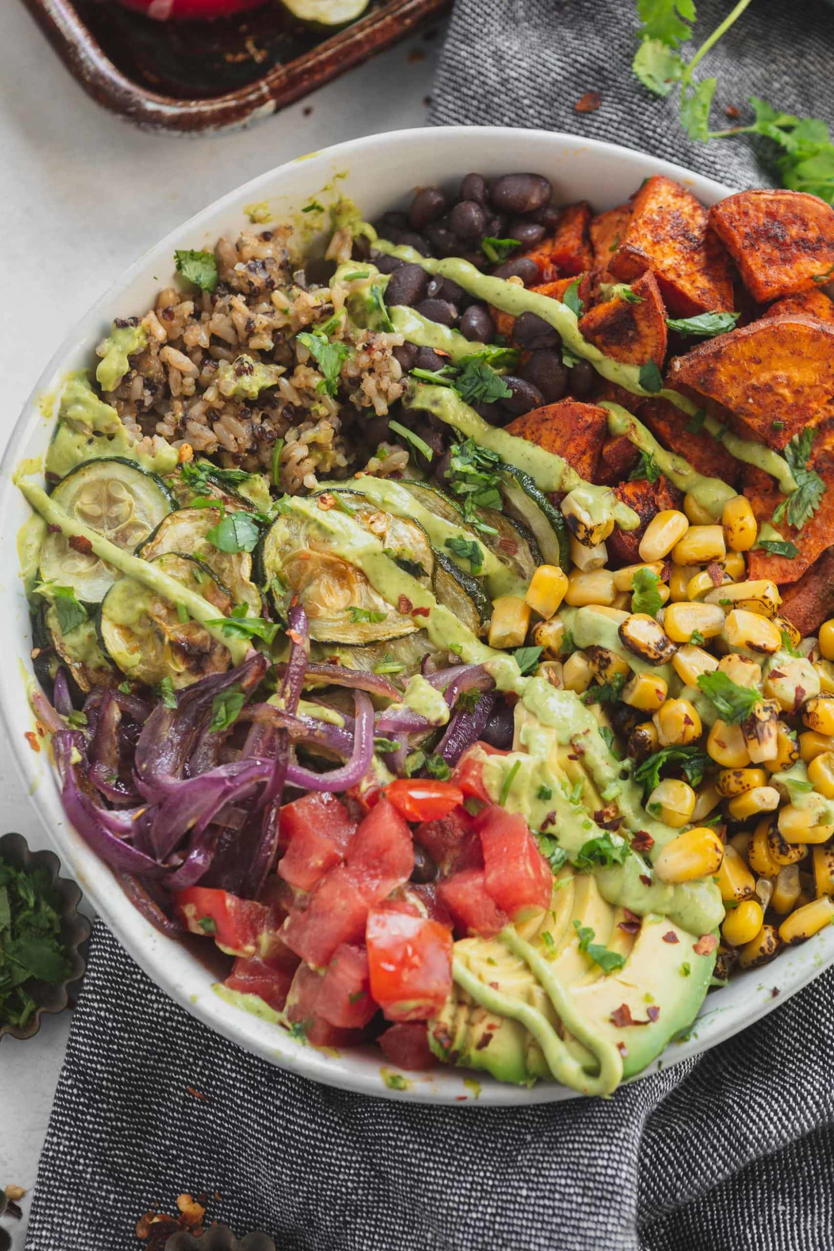 A vegan burrito bowl filled with brown rice, quinoa, roasted corn, tomatoes, black beans, red onions, zucchini and sweet potatoes.