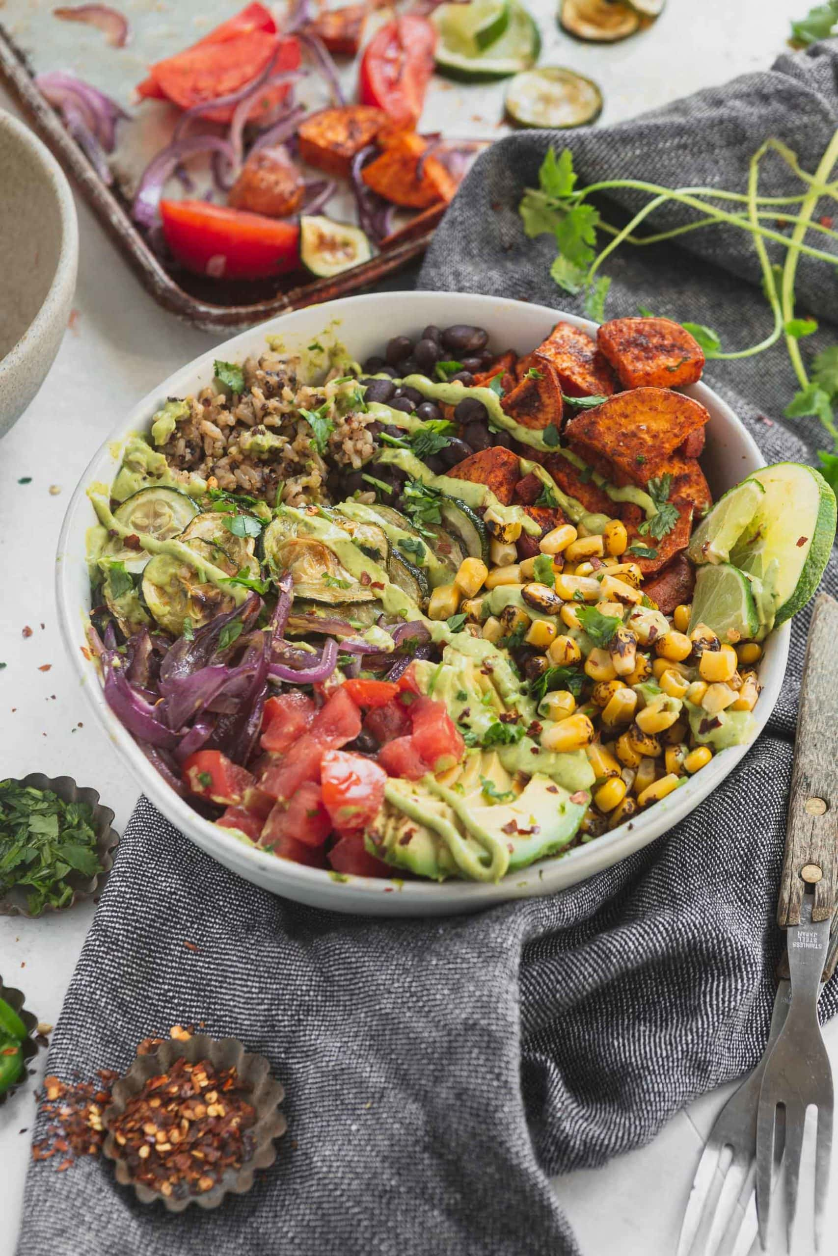 A vegan burrito bowl that contains tomatoes, avocados, roasted corn, sweet potatoes, zucchini and red onion. There is brown rice and quinoa in the burrito bowl.