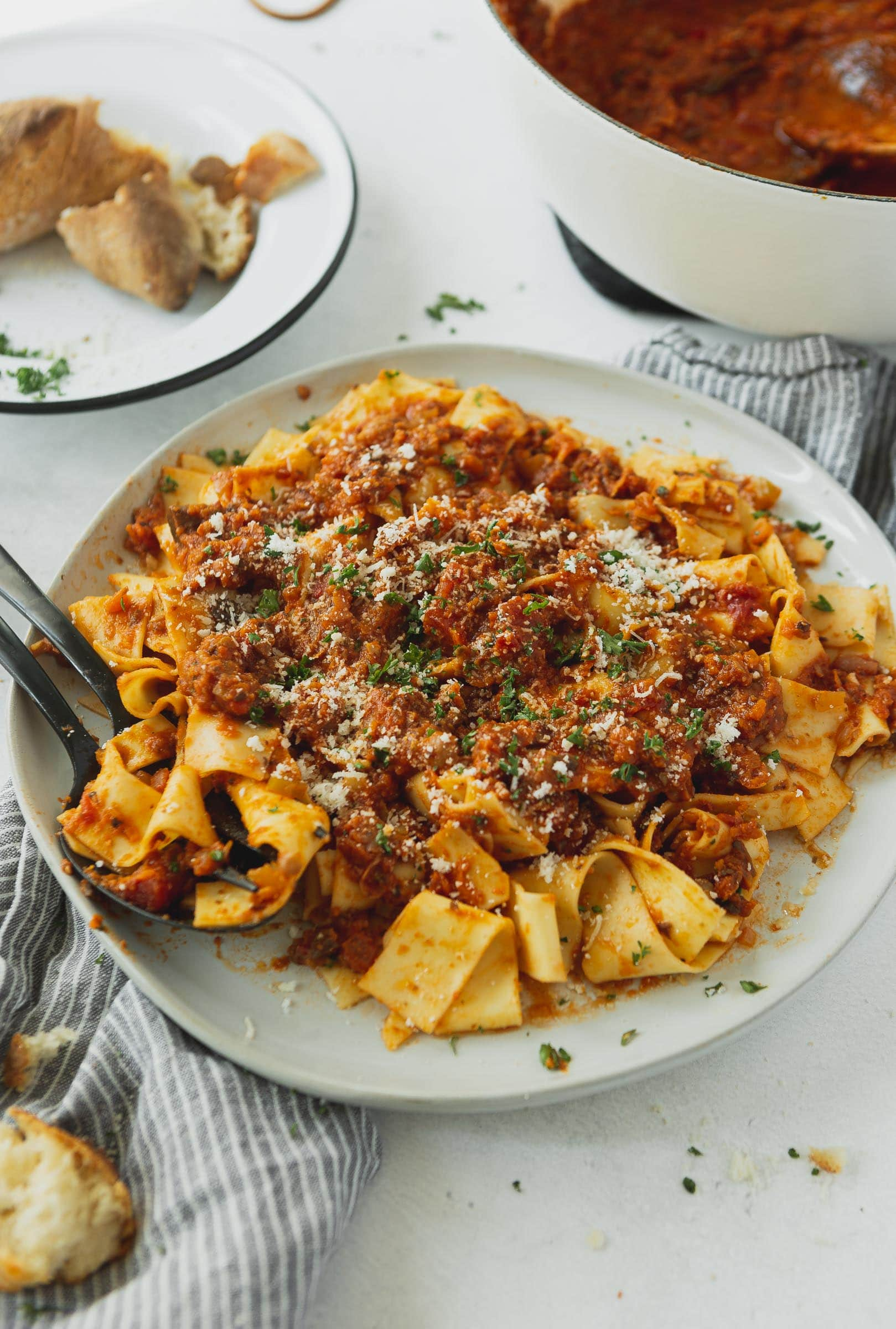 A plate full of pasta topped with vegan bolognese sauce. There is a fork on the plate and the pasta is topped with a little grated cheese and cilantro.