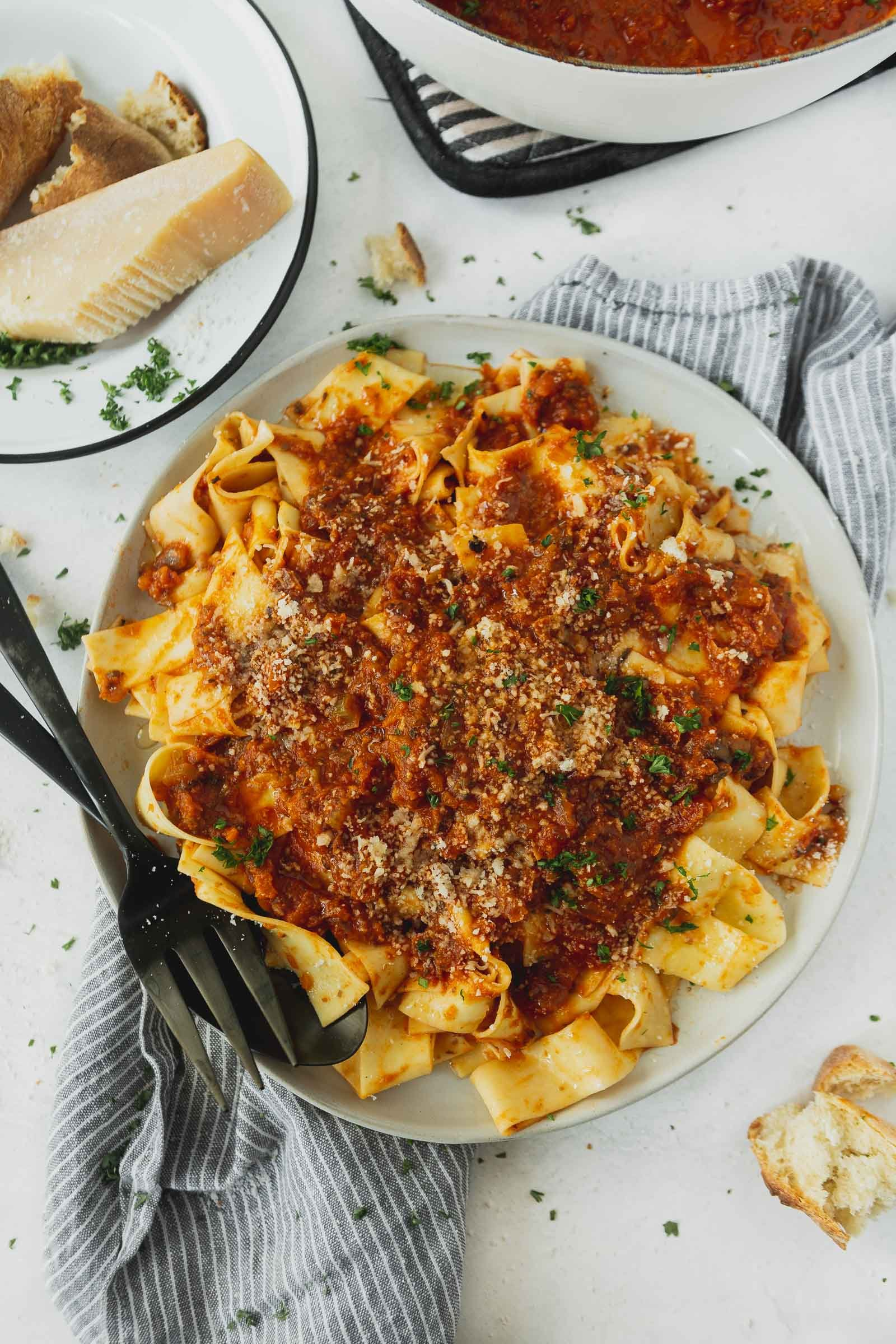 A dinner plate of pasta topped with vegan bolognese sauce, It is a thick red sauce and there are cilantro leaves sprinkled on top and a fork is on the plate next to the pasta.