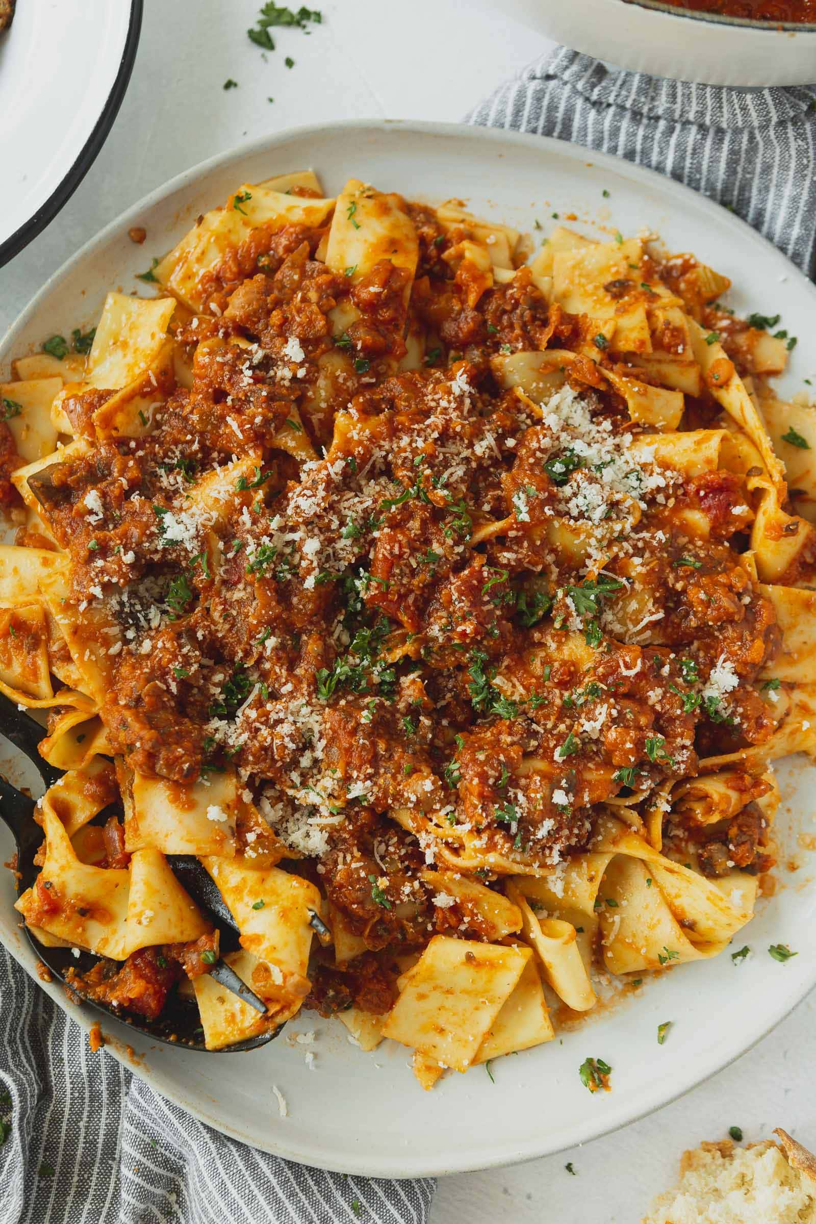 Pasta with bolognese sauce. A little grated cheese and chopped cilantro is on top.