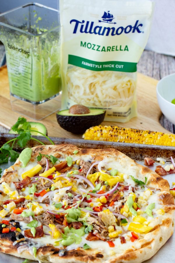 A photo of pulled pork pizza covered in sweet corn, red onions, pinapple, bacon, and fresh cilantro with a cob of grilled corn in the background as well as a bag of Tillamook mozzarella cheese shreds.