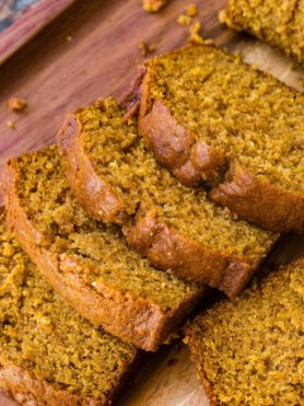 a sliced load of pumpkin bread on a wooden plattera