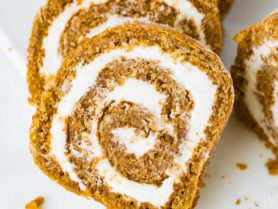 A photo of several slices of pumpkin roll with cream cheese frosting.