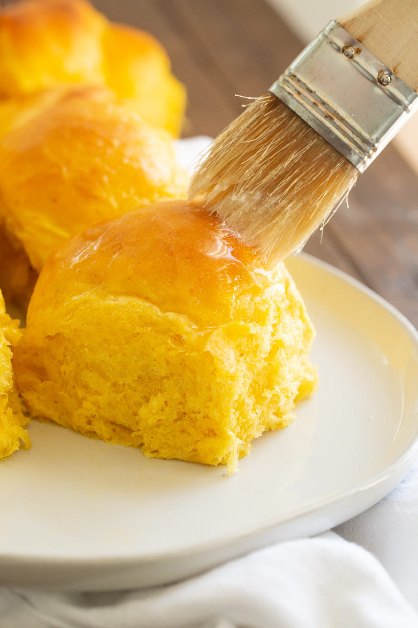 a pumpkin dinner roll being brushed with butter